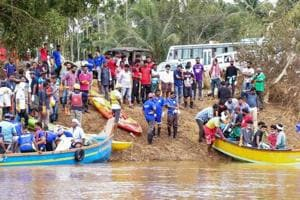 Volunteers and locals ride a boat to as they head out to clean Panamaram River, in Wayanad on  August 30, 2018.
