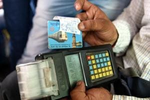 A man holds his metro card after swiping the card to pay the DTC bus fare in New Delhi on Friday.