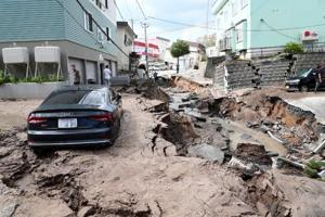 A car stuck on a road damaged by an earthquake in Sapporo, Hokkaido prefecture on September 6, 2018.