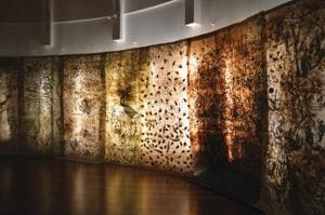 The exhibition features 18 giant scrolls — layered with dried leaves, twigs, roots and creepers — that hang from the ceiling and create a cave-like environment.