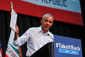 Former US president Barack Obama holds up a clipboard as he participates in a political rally for California Democratic candidates during a event in Anaheim, California.