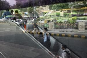 Commuters ride an escalator from Japnath metro station as vehicles are sitting in traffic are reflected in a window in New Delhi. A report Wednesday may show price pressures in August eased below 4 percent for the first time in 10 months. While that sounds like good news, a currency that's been slipping to a new record almost every day is ensuring that the optimism doesn't last too long.
