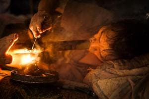 Hmong tribesman Vo Pali taking a puff of opium at his village in Houaphan province, northern Laos.