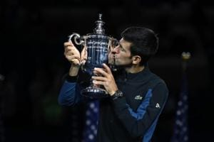 Novak Djokovic poses with the championship trophy after winning his men