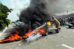 A policeman tries to douse a burning tyres during