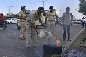 A policeman puts out a burning tyre that was set on fire by protesters during the Bharat bandh , in Mumbai on September 10, 2018.