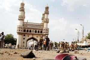 Police and members of the media walk around the Char Minar gate in Hyderabad, following a deadly blast at the nearby Macca Masjid mosque on May 18, 2007.