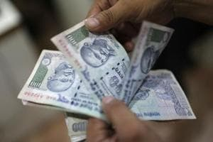 An employee counts Indian rupee currency notes inside a private money exchange office in New Delhi.