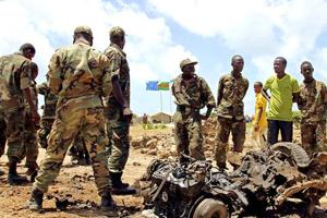 Jubaland forces and Somali residents stand near the site of a suicide car bomb attack near a military training base in the port town Kismayu.