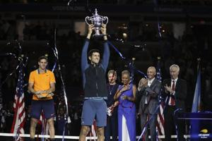 Novak Djokovic, of Serbia, holds up the championship trophy after defeating Juan Martin del Potro, of Argentina, during the men