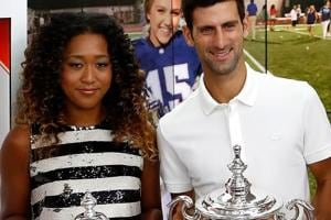 Novak Djokovic of Serbia and Naomi Osaka of Japan hold their winners trophies.