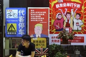 A man stands near a poster depicting a mural of US President Donald Trump, on display outside a restaurant in Guangzhou in south China