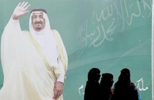 Women walk past a poster of Saudi Arabia