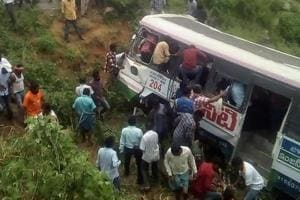 Onlookers and rescuers gather around a bus that crashed in Jagtial district in Telangana on September 11, 2018.