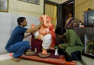 A resident of Shanti Nagar gives finishing touches to an idol of shadu clay, at Mira Road on Tuesday.