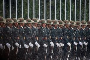Nepalese Army personnel wait in the rain to present the guard of honour to Sri Lanka
