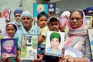 Families showing pictures of their relatives killed during militancy, in Amritsar on Wednesday.