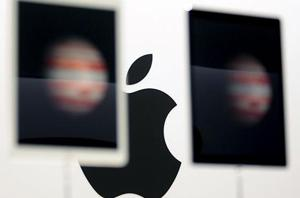 The Apple logo is seen behind new Apple iPad Pros on display during an Apple media event in San Francisco.