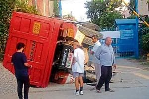 Residents said they were jolted by a loud noise, as the truck, laden with construction material, overturned at a curve after a wheel on its rear left side slipped into a stormwater drain.