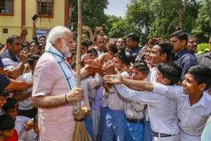Prime Minister Narendra Modi greets schoolchildren as he undertakes a cleanliness drive under