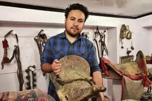 Munshi Aziz Bhat's great grandson Muzammil Hussain holds an antique horse saddle, Kargil, Jammu and Kashmir.