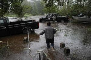 A resident walks from her flooded house towards the crew of the Cajun Navy in Lumberton, North Carolina, on September 15, 2018 in the wake of Hurricane Florence.