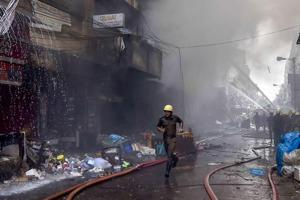 Firefighters try to douse a fire that broke out in a multi-storied wholesale Bagree market, at Burrabazar in Kolkata on Sunday.