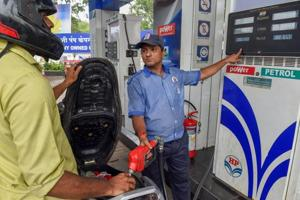 An employee shows the revised prices of petrol and diesel to a customer at a fuel station, as the fuel prices prices continued their record-breaking run, in Mumbai, Friday, September 7, 2018.