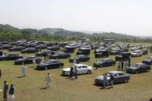 People visit an auction of government owned used cars at the premises of Prime Minister House in Islamabad.