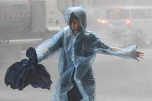 A woman runs in the rainstorm as Typhoon Mangkhut approaches, in Shenzhen, China on September 16, 2018.
