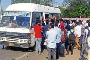Commuters crowd around a private mini bus in Jaipur on Monday as city transport workers' strike paralysed services, leaving hundreds stranded.