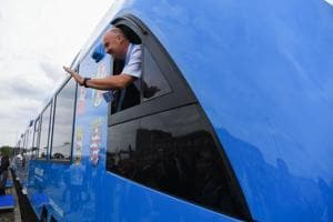 An employee of French train maker Alstom, waves from a window upon the arrival of Alstom