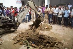 Police investigate the site where a rape victim was allegedly buried, at a government shelter home in Muzaffarpur, on July 23.