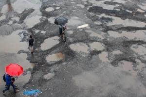 Commuters walks past potholes at Bandra Station bus stop in Mumbai.