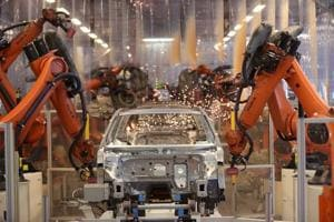 Robotic arms manufactured by Kuka AG operate on a Volkswagen Passat saloon chassis on the automated welding production line inside the VW factory in Emden, Germany, on March 9, 2018.