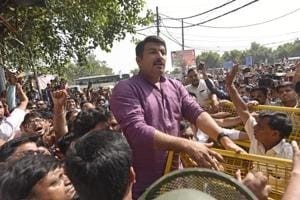 Police try to stop BJP leader Manoj Tiwari as he attempts to break the seal of a property sealed by MCD in Gokulpur area in east Delhi on Tuesday.