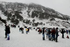 Tourists enjoy the view of snow covered hills around the Changu Lake after fresh snowfall, some 40 kilometres from Gangtok, in Sikkim.