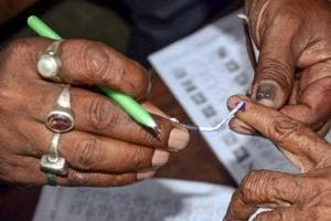 Election officials mark a voter's finger during the West Bengal panchayat polls