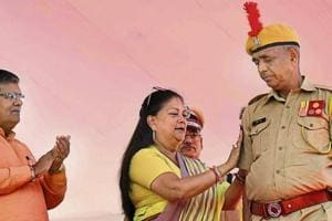 Chief minister Vasundhara Raje straps a badge on the arm of a policeman at a promotion ceremony for constables in Jaipur on Wednesday.