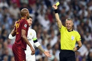 Real Madrid defender Sergio Ramos (in white) is shown a yellow card by Dutch referee Bjorn Kuipers at the Santiago Bernabeu Stadium in Madrid.