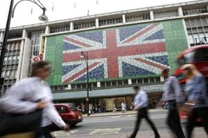 Pedestrians walk past a British Union flag design decorating the front of a John Lewis store front in Oxford Street in central London.