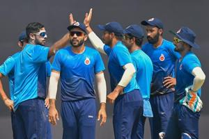 Delhi bowler Manan Sharma (L) and his teammates celebrate after taking the wicket of Saurashtra batsman Sheldon Philip Jackson (not in the picture) during the Vijay Hazare trophy cricket match, at the Ferozshah Kotla ground.