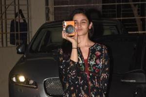 Alia Bhatt gestures as if she were taking a picture of the paparazzi.