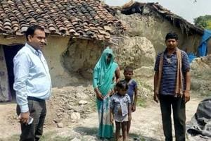 Officials of Allahabad district administration with Geeta Devi and her two children outside her house.