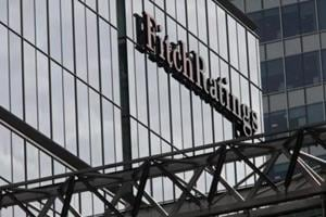 A sign sits on the glass wall of financial ratings agency Fitch Ratings in the Canary Wharf business district in London.