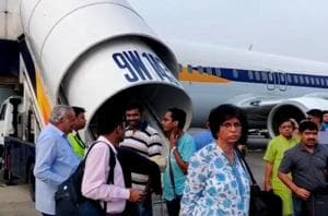 Passengers stand on the tarmac after an emergency landing, due to lost cabin pressure, on a Jet Airways flight, in Mumbai, India September 20, 2018 in this still image obtained from social media video.