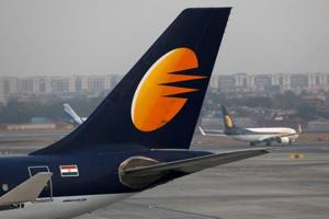 A Jet Airways plane is parked as other moves to runway at the Chhatrapati Shivaji International airport in Mumbai.