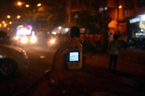 Sarita Khanchandani, the founder of NGO Hirali Foundation, holds up a sound meter to measure noise levels in Ulhasnagar.