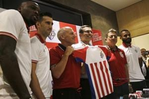 Atletico De Kolkata football club's Head coach Steve Coppell, third left, and co-owner Sanjiv Goenka, third right, unveil the team jersey for the fifth edition of the Indian Super League (ISL) as captain Manuel Lanzarote Bruno, second left, footballer Andre Bikey, left, and assistant coach Sanjouy Sen, second right, look on in Kolkata, India, Thursday, Sept. 20, 2018.