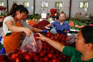 People buy fruit at a fresh food market in Beijing. China -- the world's largest market for beef, pork and poultry -- is steadily turning wary to meat as the health-conscious Chinese are taking to vegetarian diet.